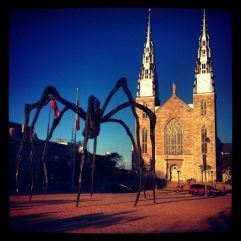 Giant spider outside National Gallery opposite a cathedral.